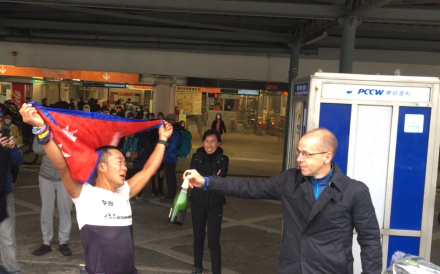 Nugo Yamanath Limbu, the first finisher at the Hong Kong Four Trails Ultra Challenge (Hk4TUC) 2020, being passed Champagne by organiser Andre Blumberg. Photo: Mark Agnew