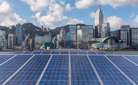 Solar panels are flanked by the Hong Kong skyline. It is already possible to reduce emissions from cities by 90 per cent using proven low-carbon measures such as solar power, mass transit and improved recycling. Photo: Shutterstock