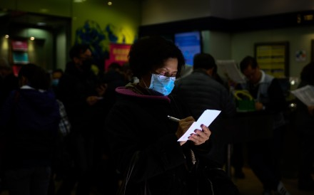 A woman wears a mask while placing her bets at a Hong Kong Jockey Club branch in Mong Kok on February 1. Photo: AFP