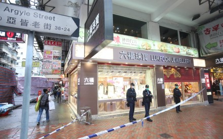 Police stand outside a Mong Kok branch of Luk Fook Jewellery, where a man who attempted to rob the store with an air gun was subdued by staff. Photo: Handout