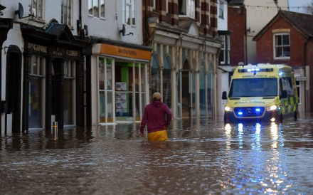 A man wades through floodwater towards an ambulance in a flooded street in Tenbury Wells. Photo: AFP