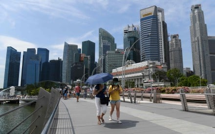 People wearing protective face masks amid fears about the spread of Covid-19, walk over the Jubilee Bridge in Singapore. Photo: AFP