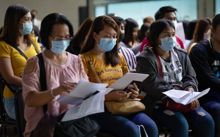Migrant workers in protective masks wait with their documents at the Philippine Trade Training Center in Pasay City on February 13, 2020. Photo: Bloomberg