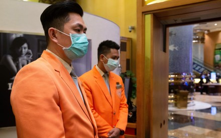 Casino workers wearing protective masks await customers as the Casino reopens in Macau. Photo: EPA-EFE