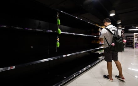 A customer stands in front of empty shelves in the toilet paper aisle of a supermarket in Singapore on February 8. Photo: Bloomberg