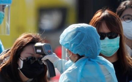 A passenger has her body temperature taken upon leaving the coronavirus-hit cruise ship Diamond Princess in Yokohama. Photo: Reuters