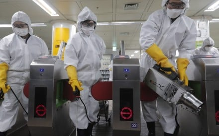 Workers in protective gear spray disinfectant at a subway station in the South Korean capital Seoul. Photo: AP