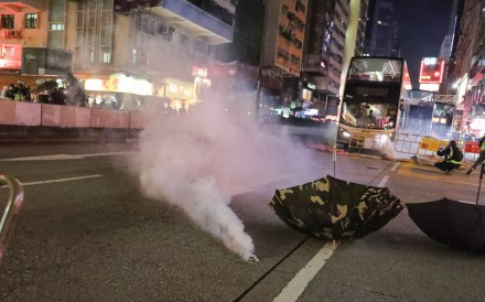 Police use tear gas to disperse anti-government protesters on Nathan Road on Saturday. Photo: Felix Wong
