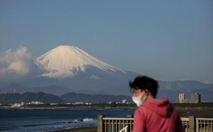 A snow-capped Mount Fuji is in the background as a mask-wearing man visits the beach. Photo: AP
