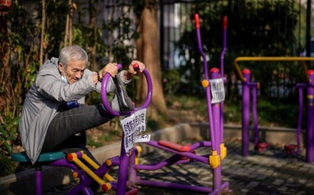 An elderly man stretches on a machine, with a sign advising residents to avoid exercising outdoors during the coronavirus outbreak, at a park in Shanghai on March 12. Photo: Reuters