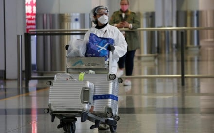 A passenger in protective suit arrives in Hong Kong, as travellers take extra precautions following the outbreak of the new Covid-19 coronavirus. Photo: Reuters