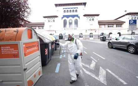 A municipal employee wearing protective gear disinfects trash bins in Vitoria, Basque Country, Spain on Tuesday. Photo: EPA-EFE