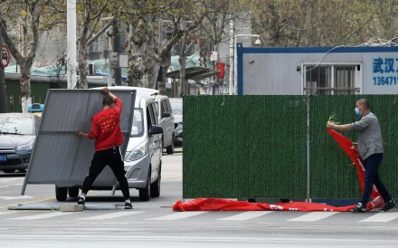 Workers remove barriers from a street in Wuhan as lockdown measures are eased. Photo: Reuters