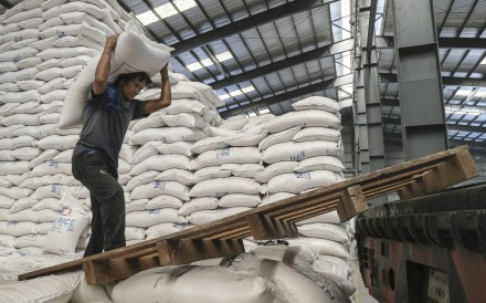 A worker carries a sack of rice inside a warehouse in Valenzuela, the Philippines. Photo: Bloomberg