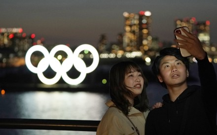 A couple take a selfie with the giant Olympic rings monument in the background at Odaiba Marine Park in Tokyo. Photo: EPA