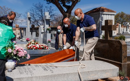 Mortuary employees bury the coffin of a coronavirus victim in Madrid. Photo: AFP