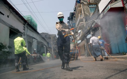 Volunteers disinfect a street as a preventive measure against the coronavirus in Yangon. Photo: AFP