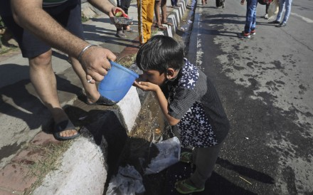 The child of a migrant daily wage labourer who has lost his job is given water by a bystander in India. Photo: AP