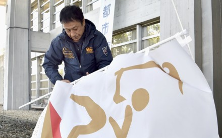 An official removes banners promoting the 2020 Tokyo Olympic torch relay at Inazawa City Hall in the Aichi prefectural city in central Japan. Photo: Kyodo