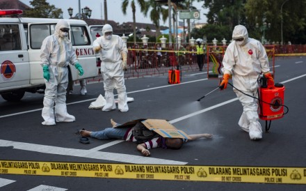 Paramedics wearing protective suits spray disinfectant on the body of a man who died suddenly on the street in Yogyakarta, Indonesia on Monday. Photo: EPA-EFE