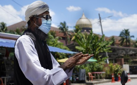 A Muslim man wearing a face mask uses hand sanitiser as he walks out from Sri Petaling Mosque in Kuala Lumpur, Malaysia on March 16. Photo: AP