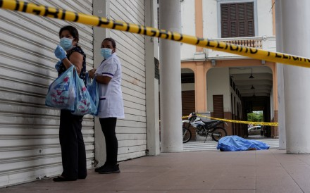 Women stand near a dead body on the pavement in Guayaquil, Ecuador. Photo: Reuters