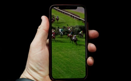A person watches the Virtual Grand National on their phone. Photo: Reuters