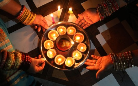Indian women light earthen lamps and candles at Jalot village, some 50km from Dharamsala, on Sunday. Photo: EPA-EFE