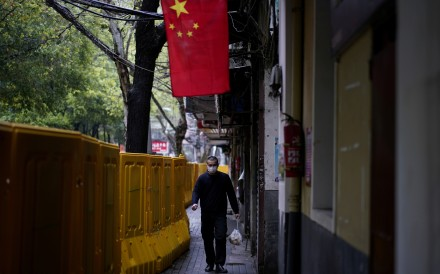 A man in a face mask walks past barriers blocking access to buildings in the central Chinese city of Wuhan, epicentre of China's coronavirus outbreak. Photo: Reuters
