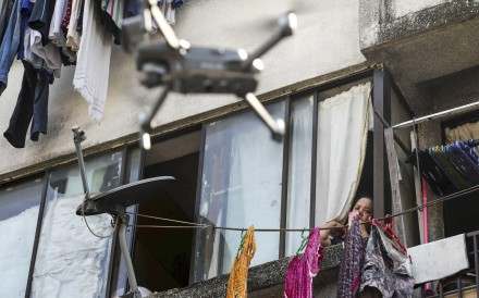 A woman watches a drone, used by the Malaysian police to remind people to stay at home during a lockdown imposed to contain the spread of Covid-19, in Kuala Lumpur on March 24. Photo: Reuters