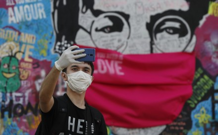 The 'Lennon Wall' with a face mask attached in Prague. The Czech government said Monday it would ease its tough anti-virus measures ahead of Easter. Photo: AP