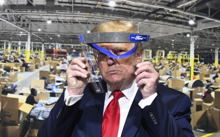 US President Donald Trump looks through a face shield, in front of a poster showing the manufacturing of the shields, while touring Ford's Rawsonville Components Plant in Ypsilanti, Michigan, on May 21. Photo: AP