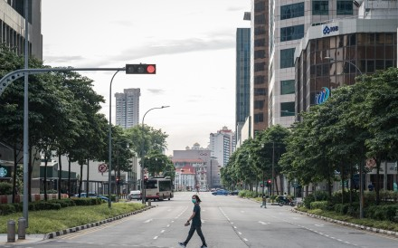 """A pedestrian wearing a mask crosses a near-empty street in the central business district during the """"circuit breaker"""" lockdown in Singapore on May 20. Singapore will allow more businesses to reopen on June 2 after a nationwide lockdown cut transmission of the coronavirus among citizens and permanent residents. Photo: Bloomberg"""