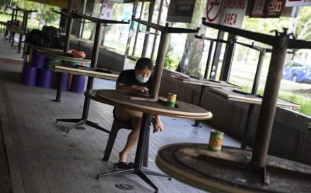 A woman wearing a protective face mask sits in an empty Singapore coffee shop where tables have been packed up to prevent people sitting down during the 'circuit breaker' partial lockdown. Photo: EPA