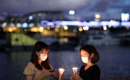 People holding candles at Kwun Tong waterfront for the annual Tiananmen candlelight vigil in Hong Kong. Photo: K.Y. Cheng
