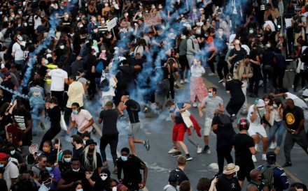 People run from tear gas as they attend a banned protest in memory of Adama Traore in Paris. Photo: Reuters