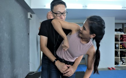 A Thai woman practices getting out of an unwanted embrace by using her elbow to strike at an assailant with hand-to-hand combat expert Kittichet Mayakarn at the latter's self-defence studio in Bangkok. Photo: Tibor Krausz