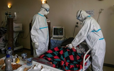Doctors in personal protective equipment (PPE) check a patient who is infected with Covid-19in Addis Ababa, Ethiopia. Photo: AFP