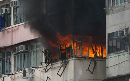 A fourth-floor flat burns inside Sham Shui Po's Dai Un Building, prompting residents to evacuate the premises. Photo: Felix Wong