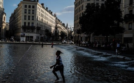 Children play in a fountain to cool off in Lyon, France. Photo: AFP