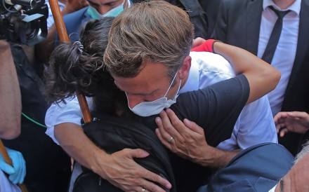 A Lebanese youth hugs French President Emmanuel Macron during a visit to the Gemmayzeh neighbourhood in Beirut. Photo: AFP