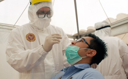 A health care worker in protective gear collects a sample during a Covid-19 swab test in Jakarta. A mutation of the virus, which was identified in February, has been circulating in Europe and the Americas before arriving in Southeast Asia. Photo: EPA-EFE