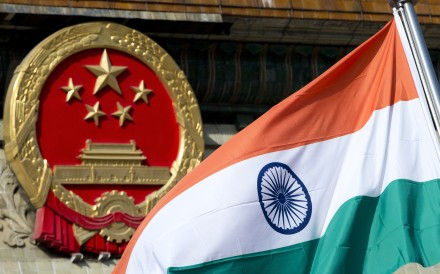 India's flag flies next to the Chinese national emblem in Beijing. Photo: AP