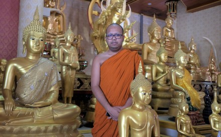 Phra Maha Paiwan Warawanno, a Buddhist monk in Thailand, stands among golden Buddha statues at Wat Soi Thong temple in Bangkok. He insists that the Buddha does not grant wishes like a genie from a lamp. Photo: Tibor Krausz