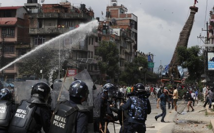 Protesters defying a government coronavirus lockdown to take part in a religious festival clash with riot police, in Lalitpur, Nepal, on Thursday. Photo: AP
