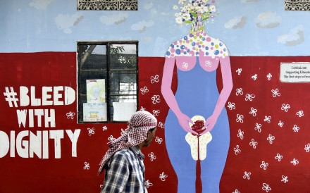 A man walks past a school wall painting about female menstruation in Guwahati, India. Photo: AFP