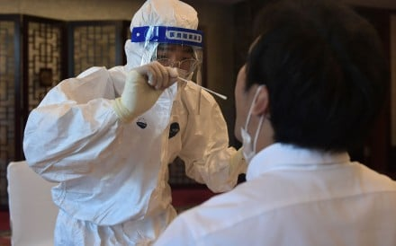 A worker in a protective suit takes a swab to test for Covid-19. Photo: AFP