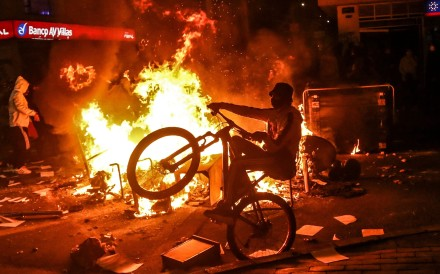 A demonstrator rides a bike at a barricade set on fire during clashes with riot police in Bogota on Thursday. Photo: AFP