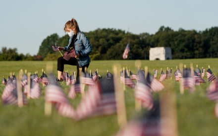 A volunteer places US flags at on the National Mall in Washington, representing some of the 200,000 lives lost during the coronavirus pandemic. Photo: Reuters