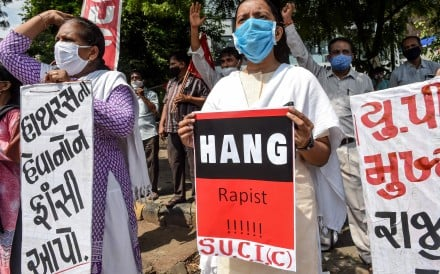 People hold placards during a protest in Ahmedabad on October 1 after the deaths of a 19-year-old and a 22-year-old woman. Photo: AFP